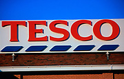A753R6 Large red Tesco sign on building with blue sky
