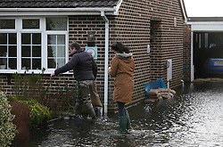 © Licensed to London News Pictures. 06/01/2014, Christchurch, UK. A resident carries a sand bag into his flooded house at Burton, Christchurch, England , Monday, Jan. 6, 2014. Part of UK continue to be affected by floods and strong wind. Photo credit : Sang Tan/LNP
