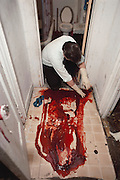 (1992) A Crime Scene Unit response to a suicide in the Bronx. A 19-year-old young man shot himself during a family argument. In the aftermath, detective Hank Fieldsa looks for a spent cartridge in the bloody gore on the floor where he shot himself. DNA Fingerprinting. MODEL RELEASED