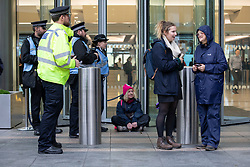 © Licensed to London News Pictures. 14/10/2019. London, UK. An Extinction Rebellion protester sits in front go the doors of the Barclays offices in Canary Wharf. Today protesters will target the financial district. Photo credit: George Cracknell Wright/LNP