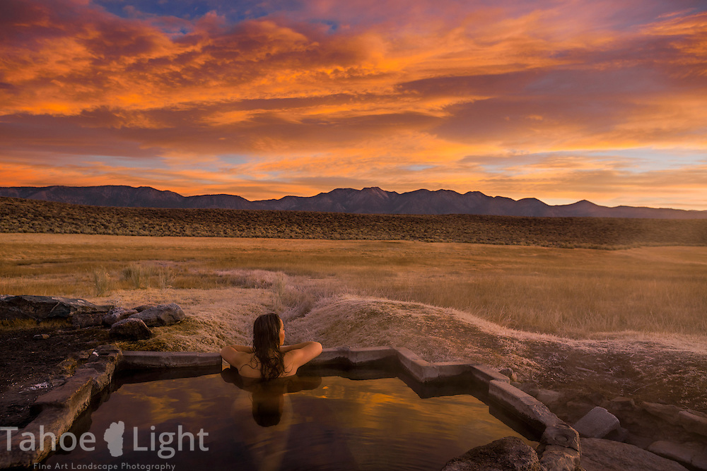 Woman watching sunrise from natural hot springs near little Alkali Lake in Owens Valley while camping near the hot springs in Mammoth, CA