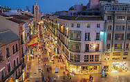 Pedestrians make their way along Calle Larios, a major shopping street in Malaga, as the sun has set and the lights come on. The view is looking from above Plaza de la Constitucion and down Calle Larios. Malaga is located along the Meditteranean coast in the Andalucian region of southern Spain.
