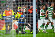 A fan is led from the pitch by stewards after Celtic score their second goal during the Europa League group stage match between Celtic and RP Leipzig at Celtic Park, Glasgow, Scotland on 8 November 2018.