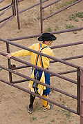 A rodeo clown helps herd bulls into appropriate pens at rodeo.
