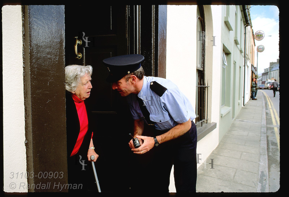 Policeman talks to old woman in doorway of her home on main street of Castletownbere; Beara Peninsula, Ireland.