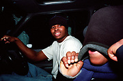 Two teenage boys in a car at night time gold tooth hood Lambeth Walk South London c.2000