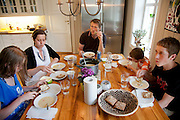 The Glad Ostensen family in Gjerdrum, Norway. Anne Glad Fredricksen, 45, her husband Anders Ostensen, 48, and their three children, Magnus, 15, Mille 12, and Amund, 8 at an evening meal in their farmhouse kitchen. Model-Released.