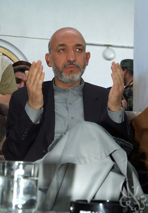 Interim Afghan leader Hamid Karzai prays with tribal elders May 04, 2002 after arriving in the southern Afghan city of Kandahar. The visit by Karzai to the city, his first since assuming power, is significant because of the city's history as a former Taliban stronghold.