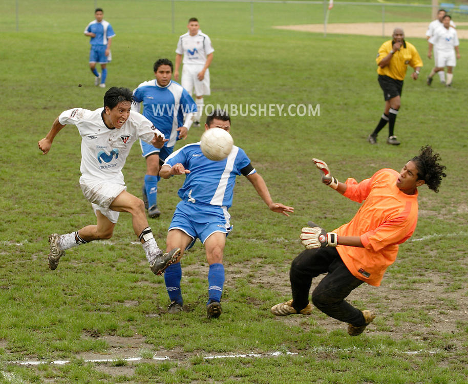 Middletown, N.Y. - A player takes a shot as the goal, at right, tries to make a save during a game at a predominantly Latino men's soccer league on Sept. 3, 2006.