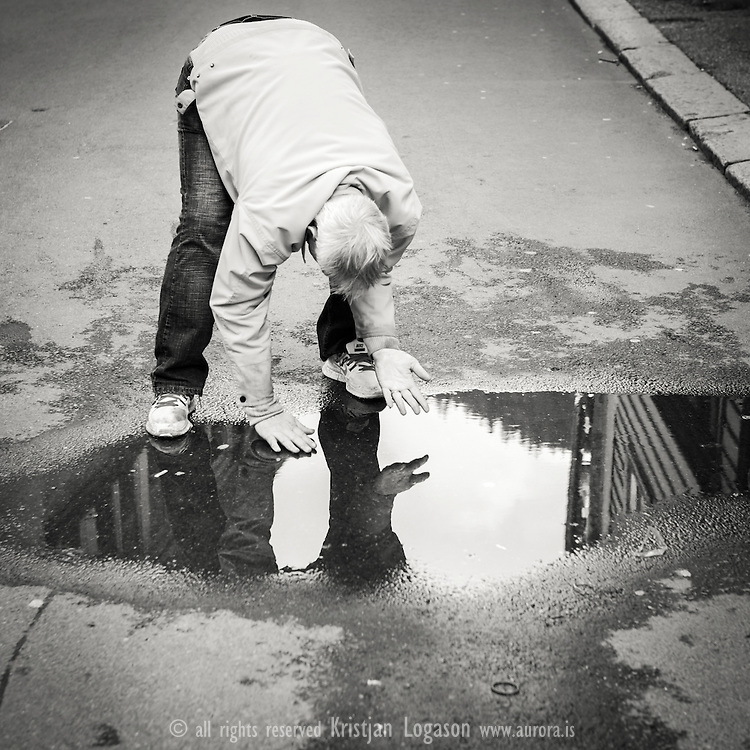 Man dressed in armani jeans, sneakers and jacket washing his hands in a street pool of water in central Bergen Norway