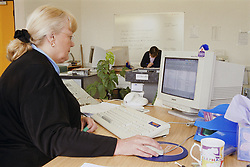 Woman working at computer in translation agency office; producing invoices,
