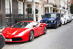 "A red ferrari and a Mercedes G Wagon share the street with a  ""marble"" £260,000 Ferrari 812 Superfast, capable of 0-60 in 2.9 seconds and £182,000 Bentley Bentayga SUV, also in ""marble"" are seen parked on Stanhope Gate near The Dorchester in Mayfair, having just been flown for their owner to the UK from Dubai. The marble effect is created by ""wrapping"" the car in printed vinyl, and is a popular method of changing the look of a car without having to have it repainted. London, August 02 2019."
