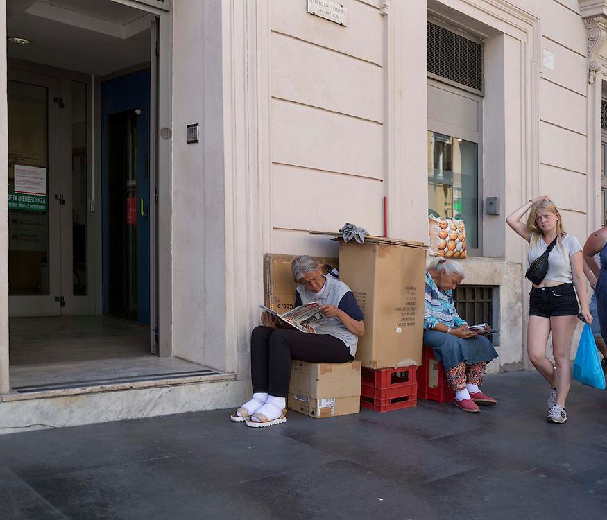 Two women clochards read the newspaper