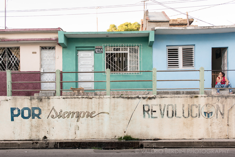 A woman sits in front of her elevated home with some old propaganda graffiti along the pavement. Cienfuegos, Cuba. 2015