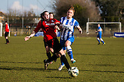 Brighton's Fliss Gibbons is tackled by Hassocks' Chloe John during the FA Women's Sussex Challenge Cup semi-final match between Brighton Ladies and Hassocks Ladies FC at Culver Road, Lancing, United Kingdom on 15 February 2015. Photo by Geoff Penn.