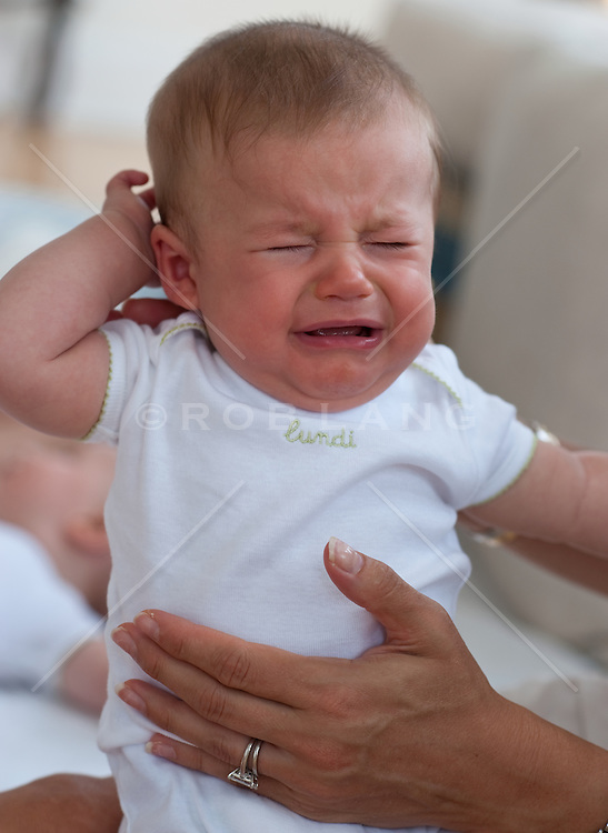 Woman's hand holding a crying baby