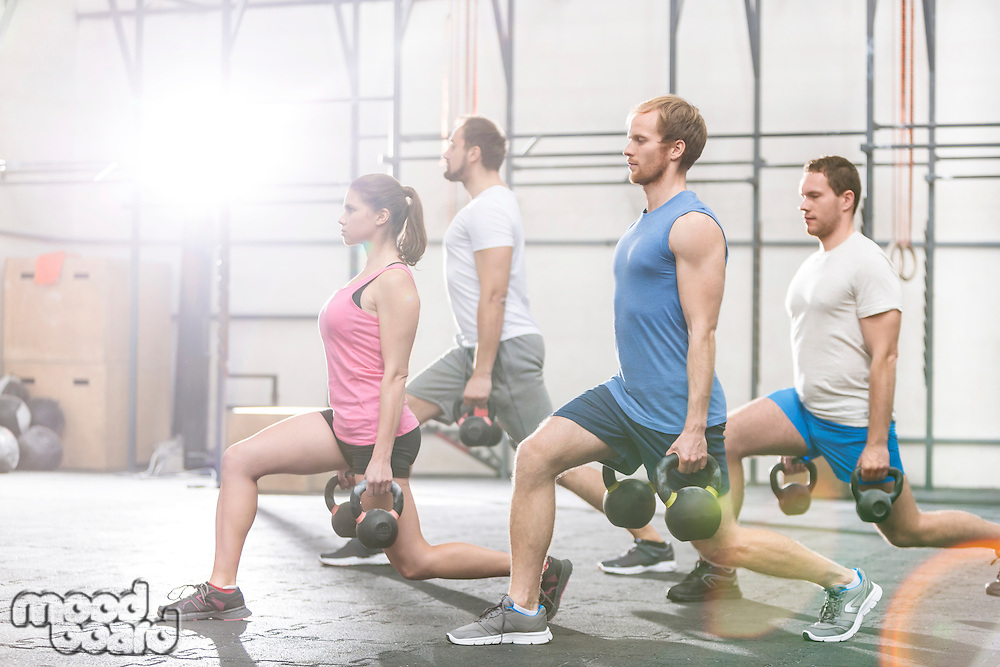 Determined people lifting kettlebells at crossfit gym