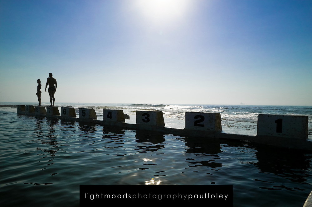 Young Couple having fun at Merewether Ocean Baths (pool) in Newcastle, Australia. Newcastle is Australia's 6th largest city about 2 hours north of Sydney.