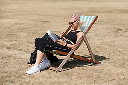 © Licensed to London News Pictures. 07/08/2018. London, UK.  A woman in a deckchair reads a book as she sunbathes in London during another day of hot and sunny weather in the capital.  Photo credit: Vickie Flores/LNP