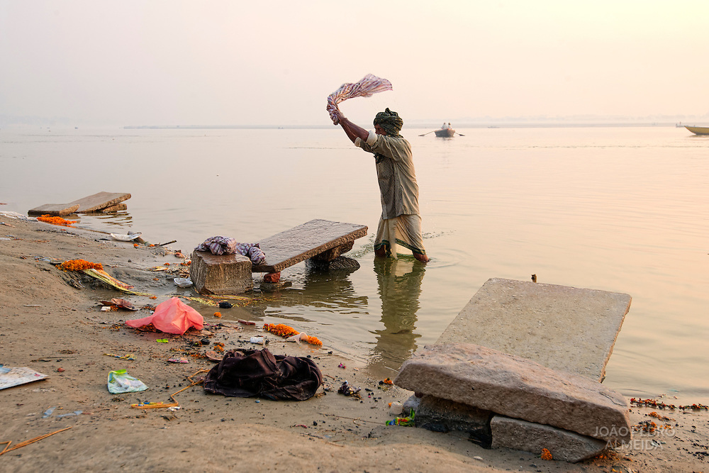 Washer washing clothes in the waters of the Ganges.