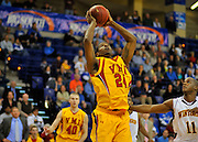 #7 VMI destroys #6 Winthrop in Big South semi-final, 75-55: VMI's sophomore center D. J. Covington scores a basket in the paint as Winthrop's Reggie King defends.  Covington led all scorers with 16 points and four blocks to lead VMI to a semi-final win in the Big South tounament in Asheville on Thursday night.