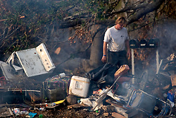 03 November, 2005. New Orleans, Louisiana. Post Katrina. <br />  Friends and family of Cory Acosta came from as far away as North Carolina to help tear out sheet rock, pick up garbage and do all they can to help people rebuild their lives in Saint Bernard parish just south of New Orleans. Hurricane Katrina caused a 20ft tidal surge to sweep over the land, devastating much of the parish. Dan Ball walks past a pile of burning trash.<br /> Photo; ©Charlie Varley/varleypix.com