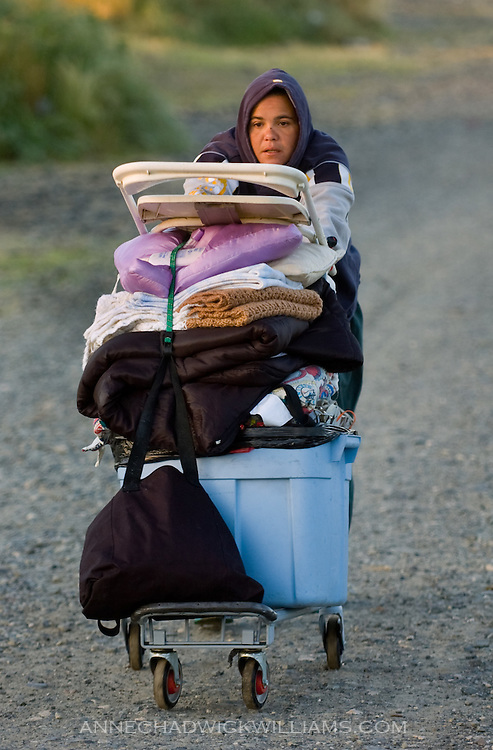 A homeless woman pushes her belongs to a new location after police moved everyone out of a tent city in Sacramento, CA.