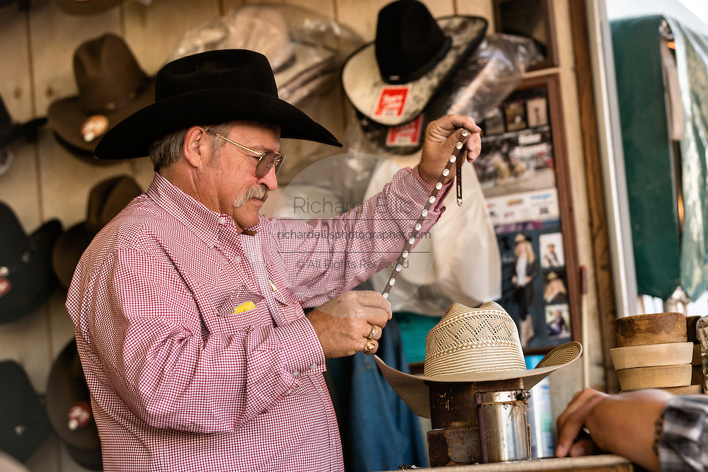 A hat shaper works on customizing a cowboy hat for a customer at Cheyenne Frontier Days July 25, 2015 in Cheyenne, Wyoming. Frontier Days celebrates the cowboy traditions of the west with a rodeo, parade and fair.