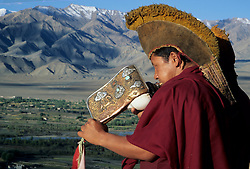 Asia, India, Ladakh, Thikse. Buddhist monk blows conch horn announcing prayers from roof of Thikse Monastery. MR