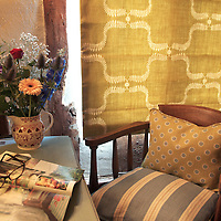 armchair and fabric furnishings in traditional house interior with desk and blind