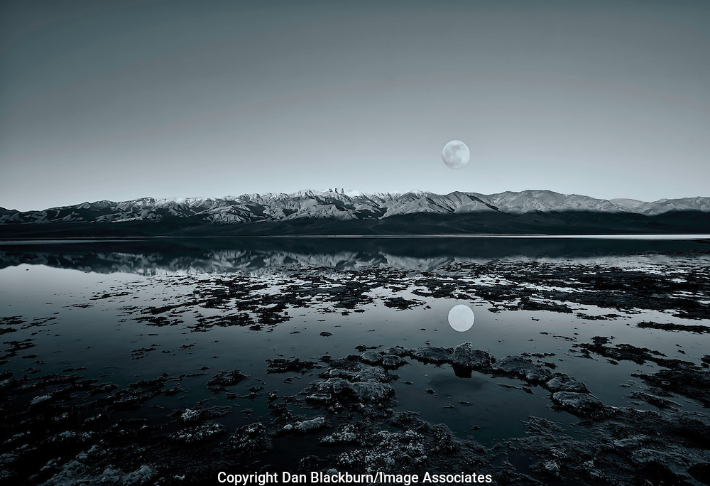 Full Moon sets over Telescope Peak in the Panamint Mountains of California and is Reflected in Badwater, the lowest point in Death Valley National Park. Blue Tint.Black&White.