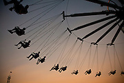 Carnival swing ride is silhouetted during Sunset at Family Kingdom amusement park along the beachfront in Myrtle Beach, SC.