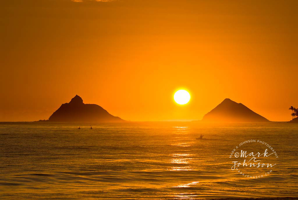Kayaking at sunrise on Kailua Bay, Mokolua Islands in bg, Oahu, Hawaii