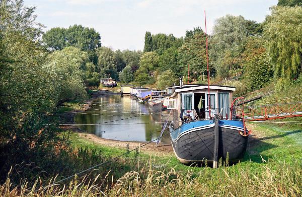 Nederland, Nijmegen, 7-8-2018De waterstand in de rivier de Waal is laag. Woonboten in een rivierarm in de buurt van de stad liggen op het droge of vallen bijna droog. Binnenvaartschepen nemen minder lading, vracht in en moeten goed in de vaargeul blijven.Foto: Flip Franssen