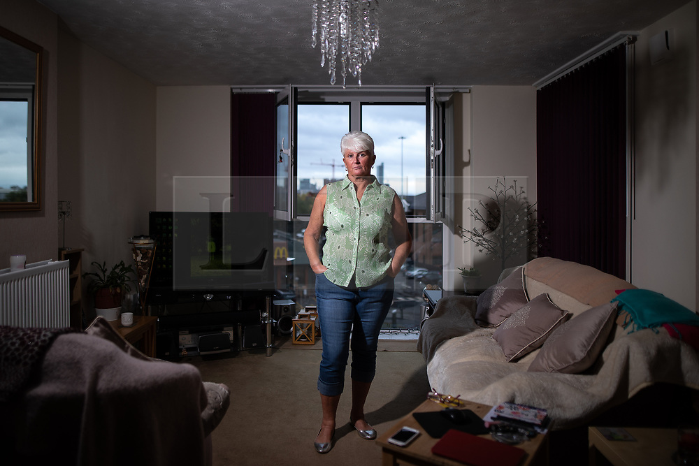 © Licensed to London News Pictures . 12/10/2018. Salford , UK . Thorn Court resident DAWN LEWIS (57) in her flat . Recently installed cladding at several council-owned tower blocks in Salford has been identified as having similar dangerous properties to that which was installed on the Grenfell Tower in London . Residents have been waiting months for clarification on what action will be taken to make their homes safe . Photo credit : Joel Goodman/LNP
