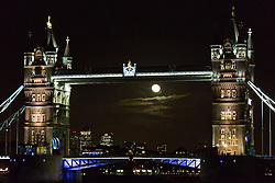 © Licensed to London News Pictures. 17/02/2014. London, UK. A near full moon rises behind Tower Bridge in London on the evening of 16th February 2014. Following a day of brilliant winter sunshine and blue sky in London, the night sky was clear other than the appearance of a single visible cloud, illuminated by the moon. Weather forecasters are predicting wet and stormy weather again from Monday. Photo credit : Vickie Flores/LNP