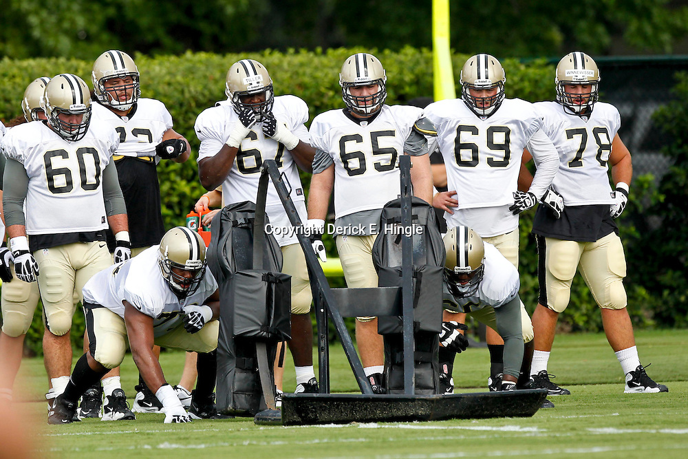 July 28, 2012; Metairie, LA, USA; New Orleans Saints guard Jahri Evans (73) and guard Ben Grubbs (66) work with a blocking sled as teammates look on during a training camp practice at the team's practice facility. Mandatory Credit: Derick E. Hingle-US PRESSWIRE