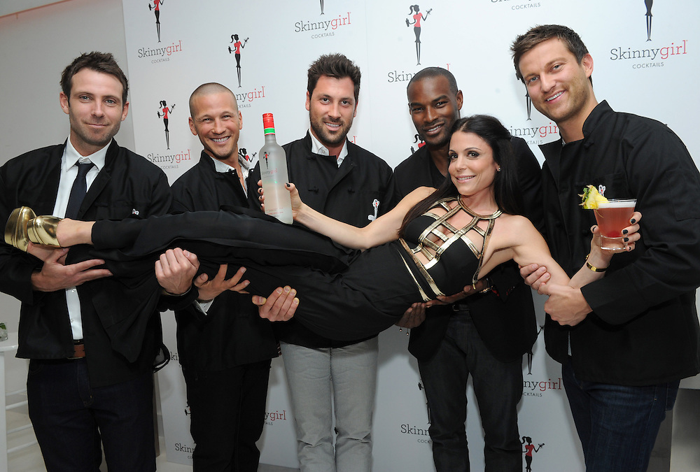 """The original Skinnygirl Bethenny Frankel strikes a pose with former """"bachelors"""" Graham Bunn and J.P. Rosenbaum, dancer Maksim Chmerkovskiy, model Tyson Beckford, and former """"bachelor"""" Chris Bukowski, left to right, at the Skinnygirl Cocktails Meet the New Girls launch party, Thursday, April 18, 2013 in New York.  The star-studded group served as the evening's mixologists, pouring the four new innovations from Skinnygirl Cocktails and donating all of their tips to Dress for Success.  (Diane Bondareff/Invision for Skinnygirl Cocktails/AP Images)"""