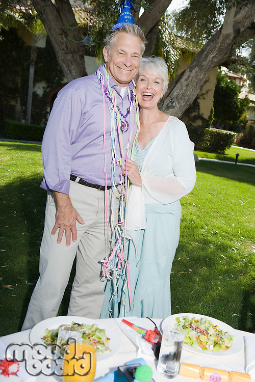 Senior couple embracing and smiling while birthday party in garden