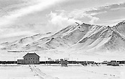 IRAN, ARAK:  Remote train station on a snowy plateau in the mountains of Iran.  Black and white dramatic landscape print.