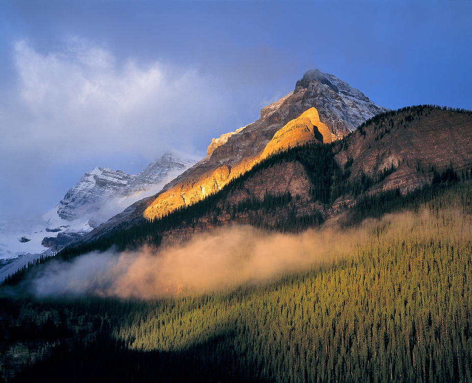 Sunrise strikes the flank of the Canadian Rockies as clouds swirl in Banff National Park, Alberta, Canada. ©Ric Ergenbright