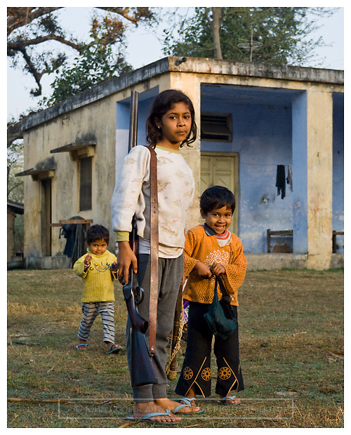 Girl with shotgun and younger brothers. Corbett National Park, Himashal Pradesh, India.