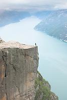 Enslig person på kanten av Preikestolen, Forsand, Rogaland. Storslått natur med utsikt over Lysefjorden. Friluftsliv.
