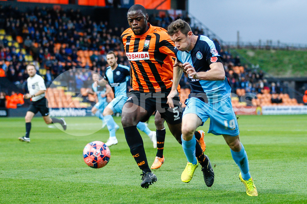 Bondz Ngala of Barnet (5) chases down Matt McClure of Wycombe Wanderers (right) during the The FA Cup 1st Round match between Barnet and Wycombe Wanderers at the Hive, London, England on 8 November 2014. Photo by David Horn.