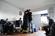 "Members of the ""Broad Channel Police Department"" greet a friend and relax after a long day of helping neighbors gut houses in their Broad Channel Community of Queens, N.Y., Nov. 3, 2012."