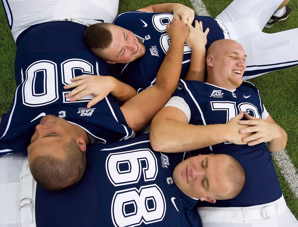 Clockwise from the left Connecticut's Tyler Bullock (50), Steve Greene, Jimmy Bennett, and Bryan Paull (68) relax while they wait their turn with the team photographer during an NCAA football media day in Storrs, Conn. (AP Photo/Jessica Hill)