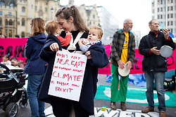 © Licensed to London News Pictures. 09/10/2019. London, UK. Parents and children take part in a Extinction Rebellion mass nursing near Westminster Abbey . Police continue to attempt to clear roads in Westminster on the third day of the protest.  Photo credit: George Cracknell Wright/LNP