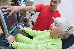 Fitness trainer showing an older woman how to use an exercise bike at the gym,