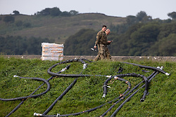 © Licensed to London News Pictures. 03/08/2019. Whaley Bridge, UK. Airmen from the RAF survey the damage from a bridge over the damaged slipway . The town of Whaley Bridge in Derbyshire remains evacuated after heavy rain caused damage to a slipway on the Toddbrook Reservoir , threatening homes and businesses with flooding. Photo credit: Joel Goodman/LNP