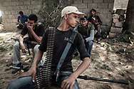 Ahead of Al Dafniya front lines, 25 km west of Misrata, Libyan rebel fighters stand by with mixed feelings as few mortar rounds fall around. 31 May 2011.